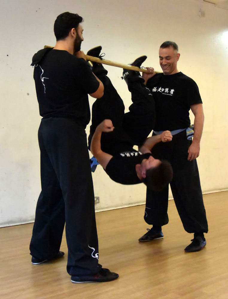 FWC Kung Fu instructors using a bar to do upside down squats