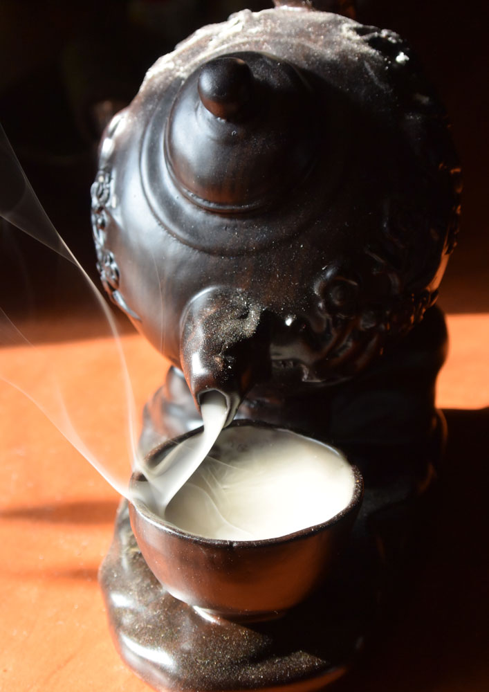 Photo of an incense burner shaped like a teapot with smoke pouring into a chinese teacup, the smoke rising from the cup looking like fish tails