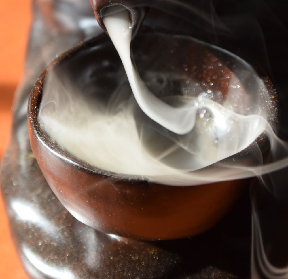Incense smoke pouring into a chinese teaciup, the smoke billowing up over the sides of the cup.