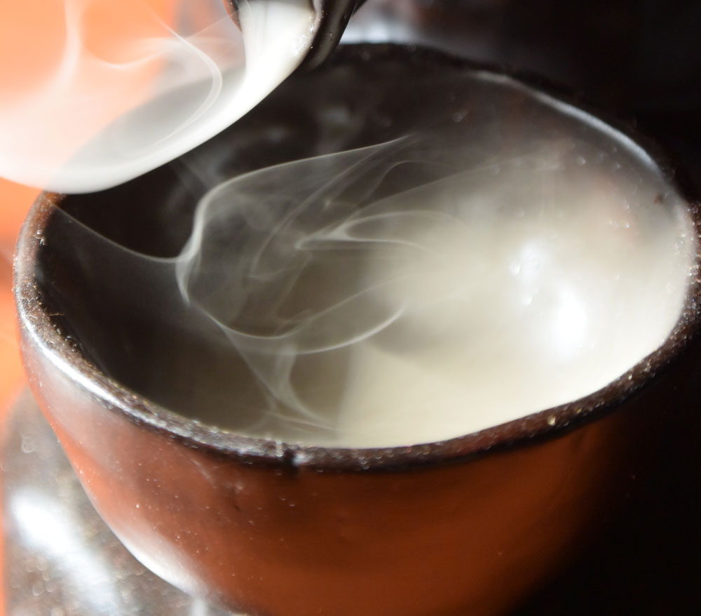 Close-up image of a red earthenware chinese teacup filling with smoke from a teapot shaped incense burner.