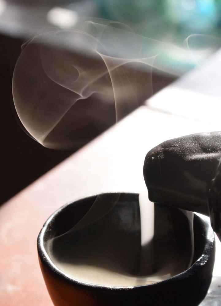 Incense smoke rising from a cup with the sunshine behind it showing the swirls in the smoke.