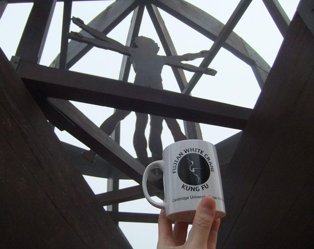 Wooden sculpture of Da Vinci's Vitruvian Man, with FWC Cambridge mug in front