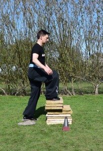 Adam steps onto the pile of paving slabs with a metronome ticking in the foreground to maintain his pace.