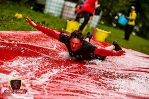 Instructor Adam Prout doing the penguin slide at the 2016 Gauntlet Games