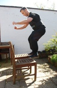 Against the background of a white brick wall Instructor Dave Courtney Jones jumping onto chairs wearing a weighted vest