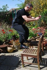Instructor Dave Courtney Jones jumps onto chairs wearing his weighted vest surrounded by the flowers in his garden