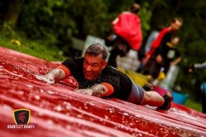 Instructor Dave Courtney-Jones doing the penguin slide at the 2016 Gauntlet Games