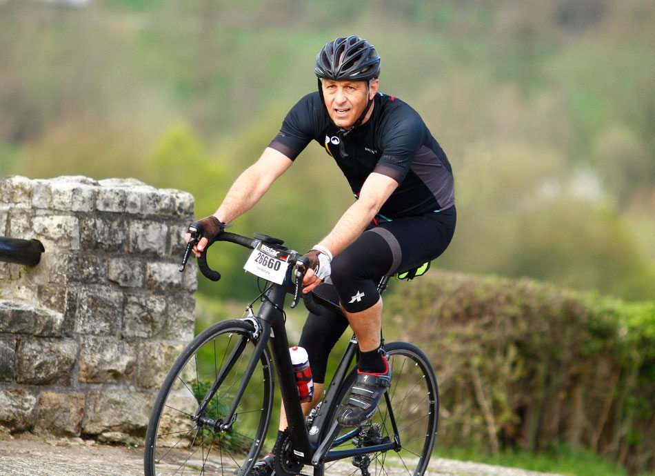 Martial Arts student and keen long-distance cyclist Pete Kelsey cycling on a country road during an endurance cycling event.