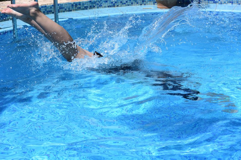 A Kung Fu student in black uniform dives into a swimming pool.