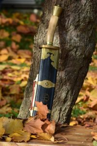 Broadsword in scabbard leaning on a tree surrounded by autumn leaves