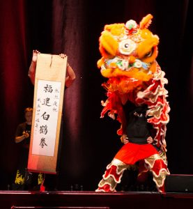 Chief Instructor Dennis Ngo holds up the Celebration Scroll as the Golden Lion dances beside him at the 40th Anniversary Celebration of the Fujian White Crane Kung Fu & Tai Chi Martial Arts Club (FWC Kung Fu)