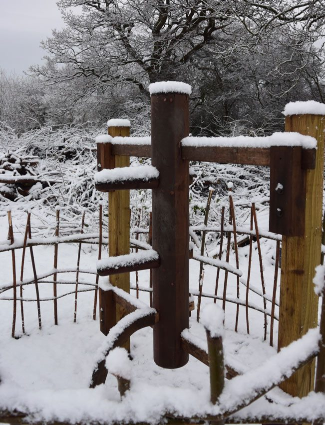 Dennis Ngo's wooden martial arts training dummy standing in a field covered in winter snow